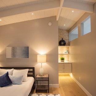 Idée de décoration pour une chambre d'amis vintage de taille moyenne avec un mur gris, un sol en bois clair et un sol marron.