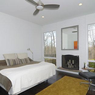 Ejemplo de dormitorio principal, actual, con paredes blancas, suelo de madera oscura, marco de chimenea de ladrillo y chimenea lineal