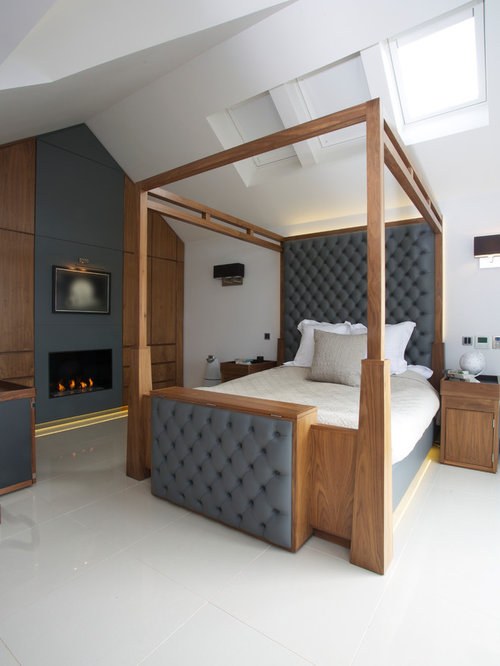 large trendy master bedroom photo in london with white walls and a standard fireplace