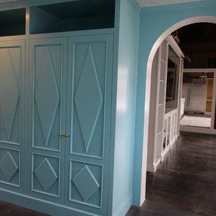 Réalisation d'une chambre parentale style shabby chic de taille moyenne avec un mur bleu et un sol en bois foncé.