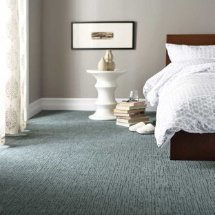 Example of a mid-sized transitional guest blue floor and carpeted bedroom design in New York with beige walls
