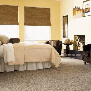 Idee per una camera degli ospiti classica di medie dimensioni con pareti gialle, moquette, camino lineare Ribbon, cornice del camino in intonaco e pavimento grigio