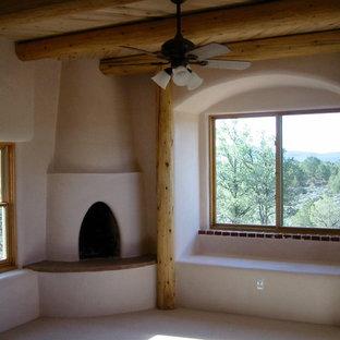アルバカーキの中くらいのエクレクティックスタイルのおしゃれな主寝室 (ベージュの壁、カーペット敷き、コーナー設置型暖炉、漆喰の暖炉まわり)