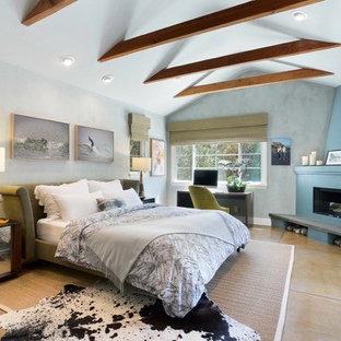 Неиссякаемый источник вдохновения для домашнего уюта: большая хозяйская спальня в средиземноморском стиле с синими стенами, бетонным полом, угловым камином, фасадом камина из штукатурки и коричневым полом