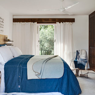 This is an example of a mid-sized beach style master bedroom in Other with white walls, terra-cotta floors and no fireplace.