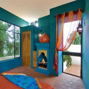 Inspiration för amerikanska sovrum, med blå väggar, klinkergolv i terrakotta, en standard öppen spis och rött golv