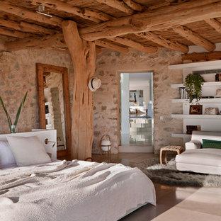 Ejemplo de dormitorio principal, rural, de tamaño medio, sin chimenea, con paredes marrones y suelo de baldosas de cerámica