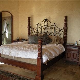 Modelo de dormitorio tipo loft, de estilo americano, de tamaño medio, con paredes amarillas y suelo de baldosas de terracota