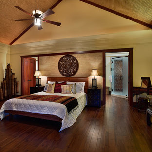 This is an example of a large asian master bedroom in Hawaii with yellow walls, medium hardwood floors, no fireplace and brown floor.