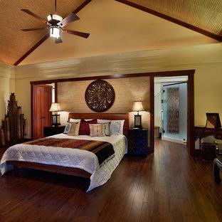 Cette image montre une grande chambre parentale asiatique avec un mur jaune, un sol en bois brun, aucune cheminée et un sol marron.