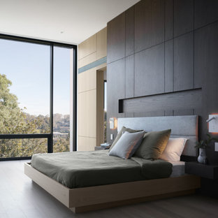 Design ideas for an expansive modern master bedroom in Sydney with light hardwood floors, beige floor and brown walls.