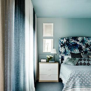 Cette photo montre une grand chambre bord de mer avec un mur bleu, aucune cheminée et un sol bleu.