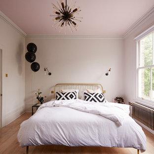 Ejemplo de dormitorio nórdico, de tamaño medio, con paredes rosas, suelo de madera en tonos medios y suelo marrón