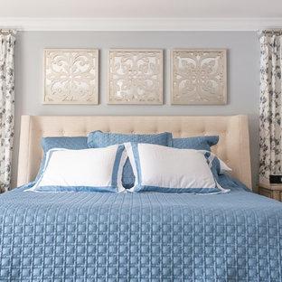 Imagen de dormitorio principal, de estilo de casa de campo, de tamaño medio, con chimenea tradicional, marco de chimenea de piedra, suelo marrón, paredes grises y suelo de madera en tonos medios