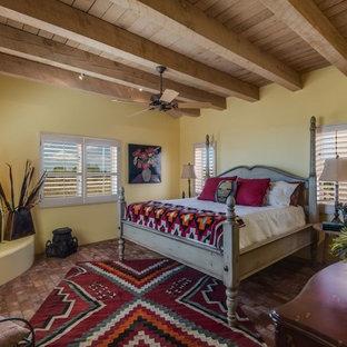 Пример оригинального дизайна: хозяйская спальня среднего размера с желтыми стенами, кирпичным полом, угловым камином, фасадом камина из штукатурки и коричневым полом