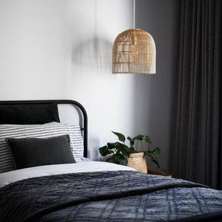 Modelo de dormitorio principal, minimalista, de tamaño medio, con paredes blancas, suelo de madera clara, chimenea de doble cara, marco de chimenea de yeso y suelo beige