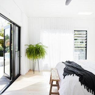 Modelo de dormitorio principal, moderno, de tamaño medio, con paredes blancas, suelo de madera clara, chimenea de doble cara, marco de chimenea de yeso y suelo beige