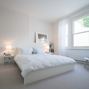 Trendy carpeted bedroom photo in London with white walls