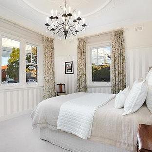 Modelo de dormitorio principal, tradicional, de tamaño medio, con parades naranjas y suelo de baldosas de cerámica