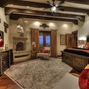 Diseño de dormitorio principal, mediterráneo, extra grande, con paredes beige, suelo de madera oscura, chimenea de esquina y marco de chimenea de hormigón