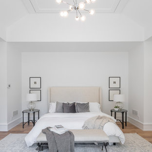 Country master medium tone wood floor and brown floor bedroom photo in New York with white walls
