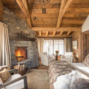 Modelo de dormitorio rural con paredes beige, suelo de madera en tonos medios, chimenea de esquina y marco de chimenea de piedra
