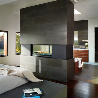 This is an example of a mid-sized contemporary master bedroom in Toronto with a two-sided fireplace, white walls, dark hardwood floors, a stone fireplace surround and brown floor.