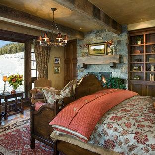 Inredning av ett rustikt sovrum, med beige väggar, mellanmörkt trägolv, en standard öppen spis och en spiselkrans i sten