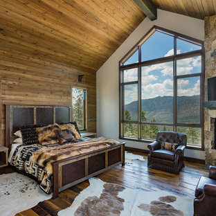 Design ideas for a large country master bedroom in Denver with medium hardwood floors, a corner fireplace, a stone fireplace surround and white walls.