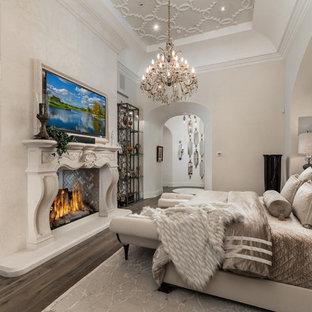 Modelo de dormitorio principal, clásico, extra grande, con paredes multicolor, suelo de madera oscura, chimenea de doble cara, marco de chimenea de piedra y suelo multicolor