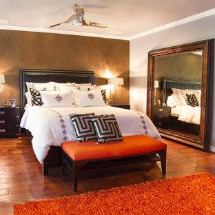 Esempio di una grande camera matrimoniale boho chic con pareti grigie, pavimento in legno massello medio, cornice del camino in pietra e camino classico