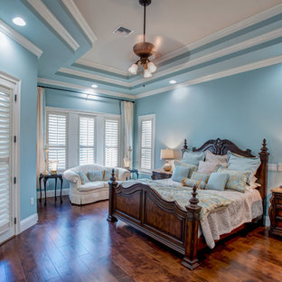 Large transitional master dark wood floor and brown floor bedroom photo in Orlando with blue walls and no fireplace