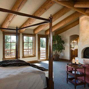 Diseño de dormitorio principal, rural, grande, con paredes beige, moqueta, chimenea tradicional y marco de chimenea de yeso