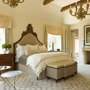 Foto de dormitorio principal, clásico, con paredes beige, chimenea de doble cara, marco de chimenea de piedra y suelo beige