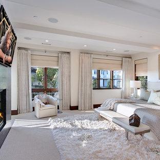 Imagen de dormitorio principal, contemporáneo, grande, con paredes blancas, moqueta, chimenea tradicional y marco de chimenea de yeso