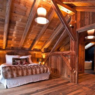 Idée de décoration pour une grande chambre parentale chalet avec un sol en bois foncé et un mur marron.