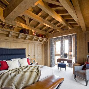 Idée de décoration pour une grande chambre parentale chalet avec aucune cheminée.