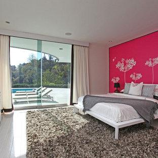 Ispirazione per una camera da letto moderna con pavimento in legno verniciato