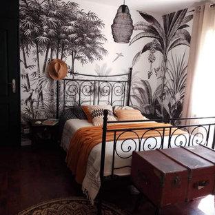 Foto de dormitorio principal, tropical, con paredes negras y suelo laminado
