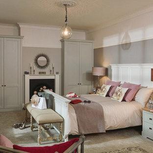 Foto de habitación de invitados tradicional, de tamaño medio, con paredes beige, suelo laminado, chimenea tradicional y marco de chimenea de madera