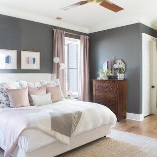 Modelo de dormitorio principal, clásico renovado, de tamaño medio, con paredes grises y suelo de madera clara