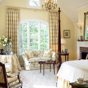 На фото: хозяйские спальни среднего размера в классическом стиле с желтыми стенами, ковровым покрытием, стандартным камином и фасадом камина из кирпича