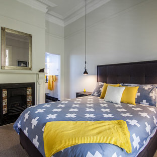 This is an example of a transitional bedroom in Hobart with grey walls, carpet, a standard fireplace and brown floor.