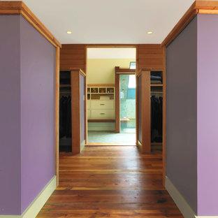 Modelo de dormitorio principal, rústico, grande, con paredes púrpuras y suelo de madera oscura
