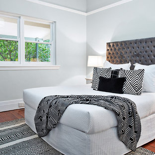 Design ideas for a mid-sized transitional master bedroom in Sydney with grey walls, medium hardwood floors and brown floor.