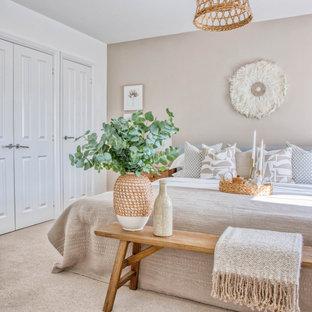 Mittelgroßes Uriges Hauptschlafzimmer mit beiger Wandfarbe, Teppichboden und beigem Boden in Devon