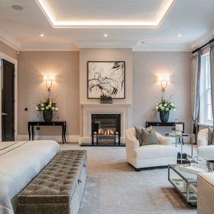 This is an example of a traditional master bedroom in Berkshire with beige walls, carpet, a standard fireplace, a stone fireplace surround and beige floors.