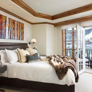 Ejemplo de dormitorio principal, rústico, grande, sin chimenea, con paredes blancas y moqueta