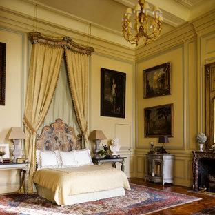 Réalisation d'une grand chambre parentale tradition avec un mur jaune, un sol en bois brun et une cheminée standard.