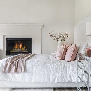 Esempio di una camera da letto stile marinaro con pareti bianche, parquet scuro, camino classico e pavimento marrone